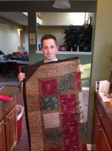 Nathan standing with finished quilt